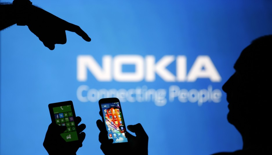 Men are silhouetted against a video screen with an Nokia logo as he poses with an Nokia Lumia 820 and Samsung S4 smartphones in this photo illustration taken in the central Bosnian town of Zenica, August 14, 2013. REUTERS/Dado Ruvic (BOSNIA AND HERZEGOVINA - Tags: BUSINESS TELECOMS)