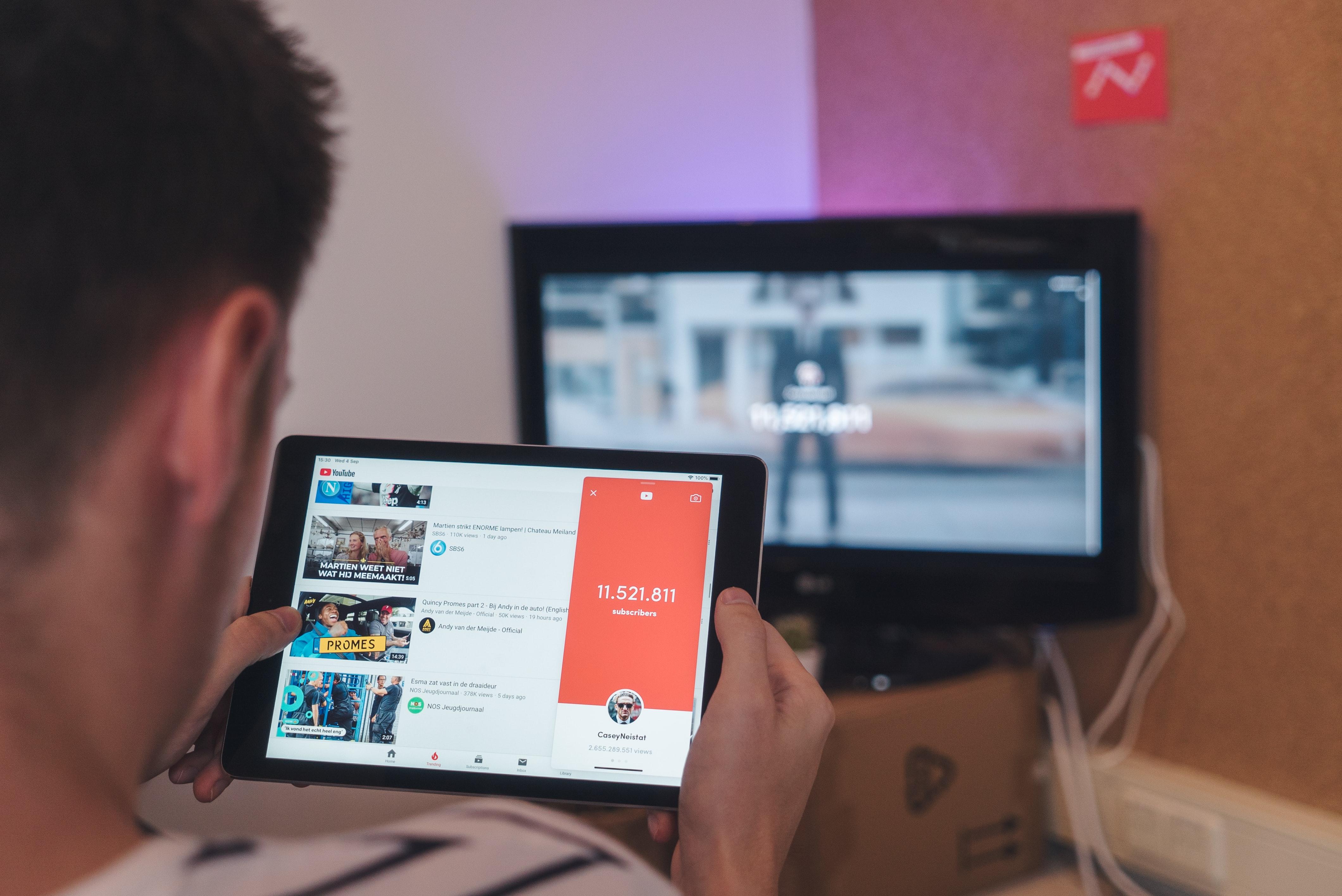 ragazzo preferisce il tablet alla TV streaming in quarantena